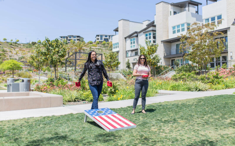 Two people play bean bag toss outside in the garden.