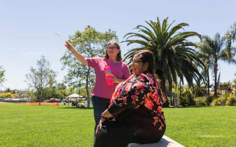 A caregiver and client enjoy a day together in the garden.